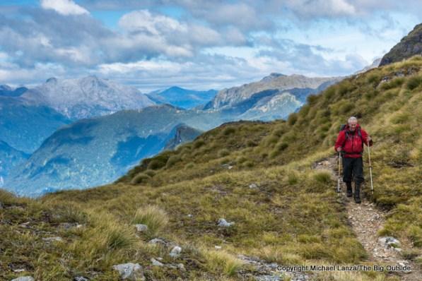A trekker at Centre Pass on the Dusky Track, Fiordland National Park, New Zealand.