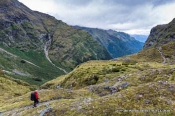 A trekker descending from Centre Pass on the Dusky Track, Fiordland National Park, New Zealand.