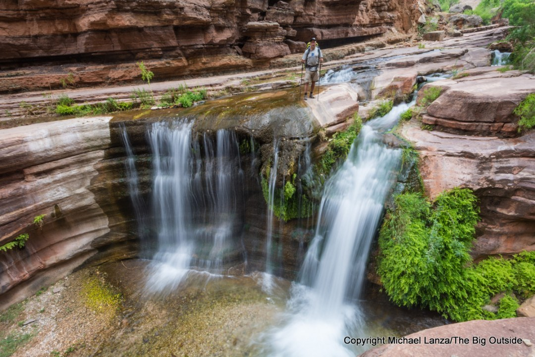 A backpacker at a waterfall on the Deer Creek Trail in the Grand Canyon.