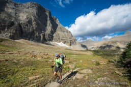 A backpacker hiking to Triple Divide Pass in Glacier National Park.