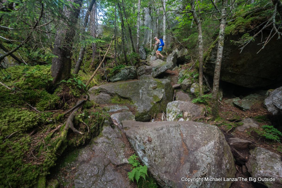 A hiker going through Mahoosuc Notch on the Appalachian Trail, Mahoosuc Range, Maine.