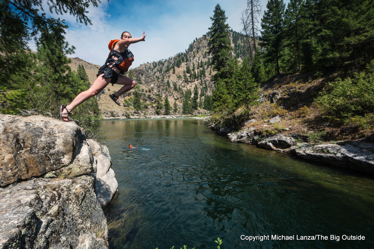 A teenage girl cliff jumping into Idaho's Middle Fork Salmon River.