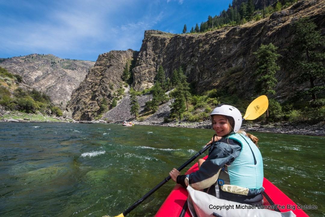 A teenage girl paddling an inflatable kayak on the Middle Fork Salmon River, Idaho.