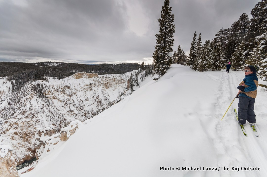A child cross-country skiing along the rim of the Grand Canyon of the Yellowstone River in Yellowstone National Park.