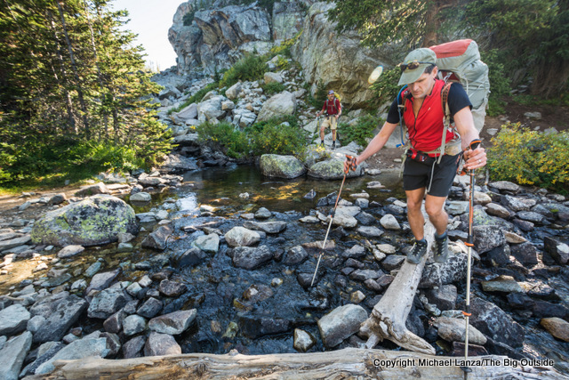 A backpacker crossing a log over a creek in Wyoming's Wind River Range.