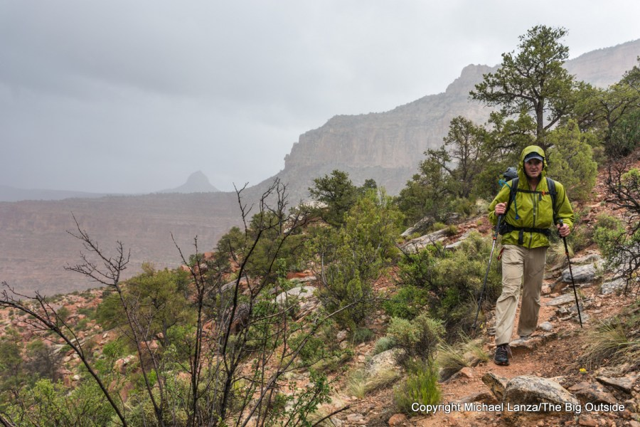 A backpacker hiking through rain showers on the Grand Canyon's Royal Arch Loop.