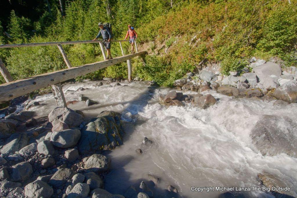 Backpackers crossing the bridge over Fryingpan Creek along the Wonderland Trail in Mount Rainier National Park.