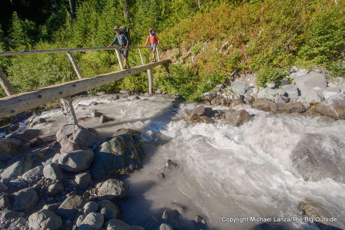 Backpackers crossing Fryingpan Creek on the Wonderland Trail, Mount Rainier National Park.