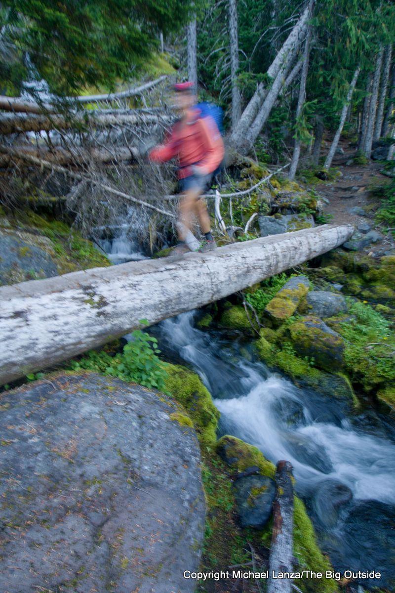 A backpacker passing Garda Falls on the Wonderland Trail, Mount Rainier National Park.