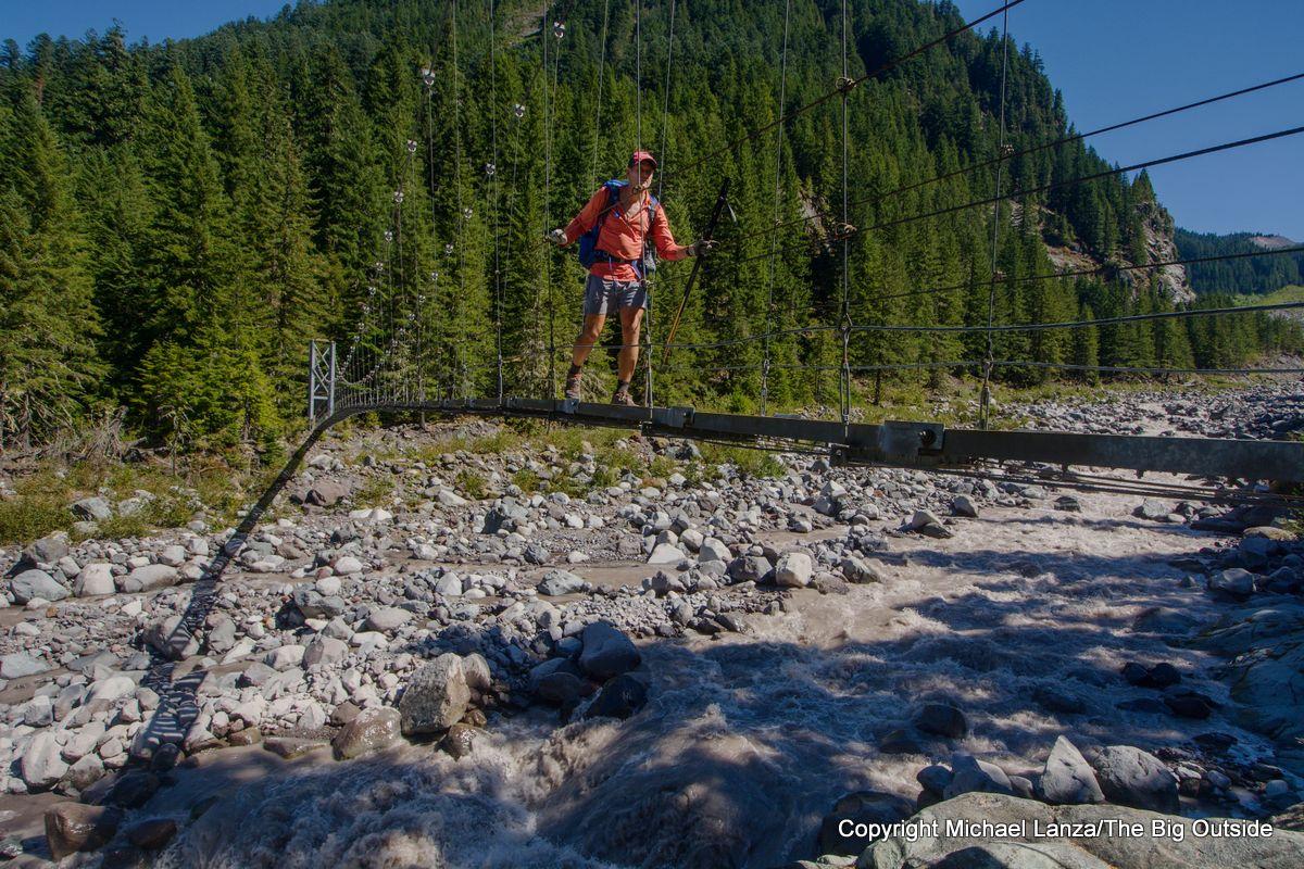 A backpacker crossing the Carbon River suspension bridge on the Wonderland Trail, Mount Rainier National Park.