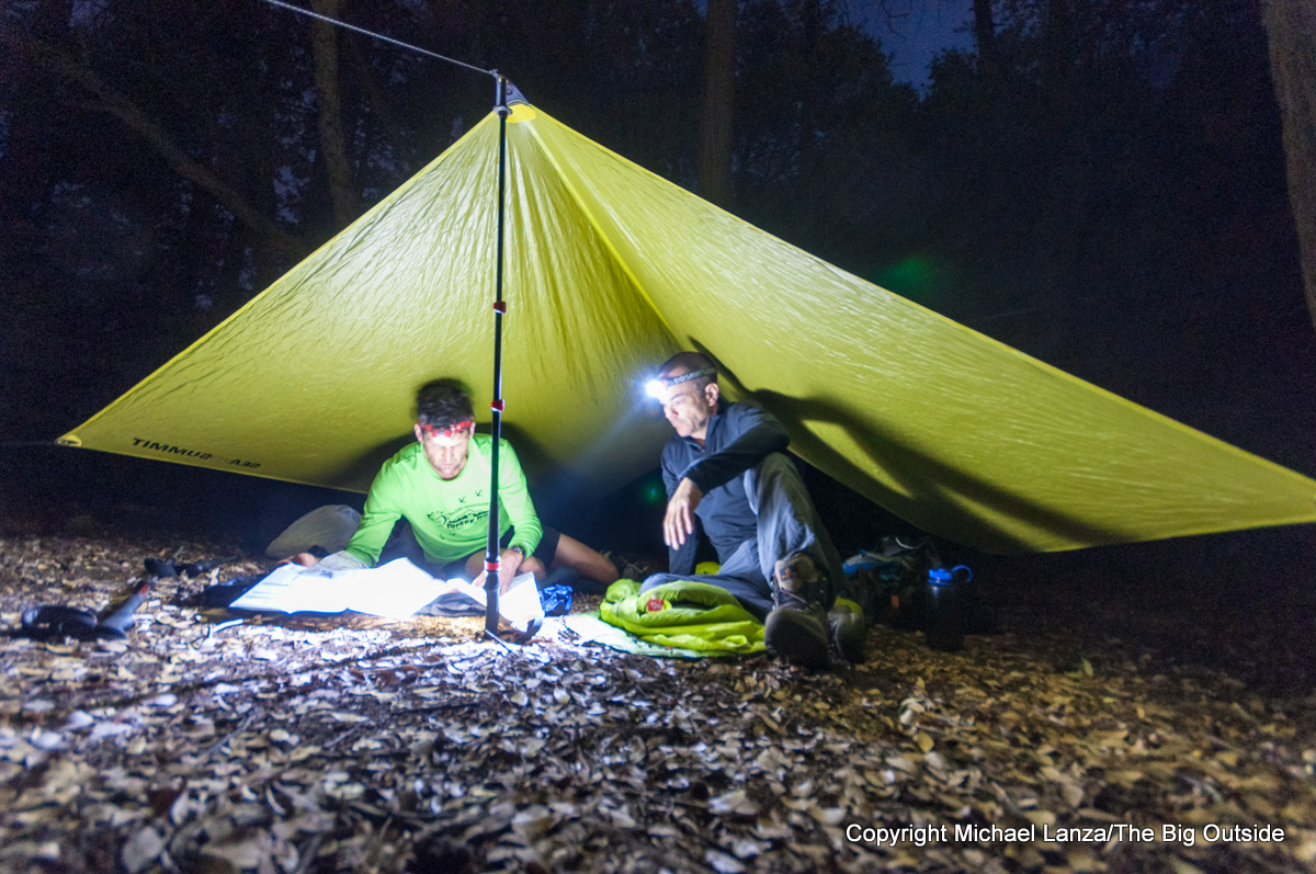Backpackers at night with headlamps in a campsite in the Grand Canyon of the Tuolumne River, Yosemite National Park.