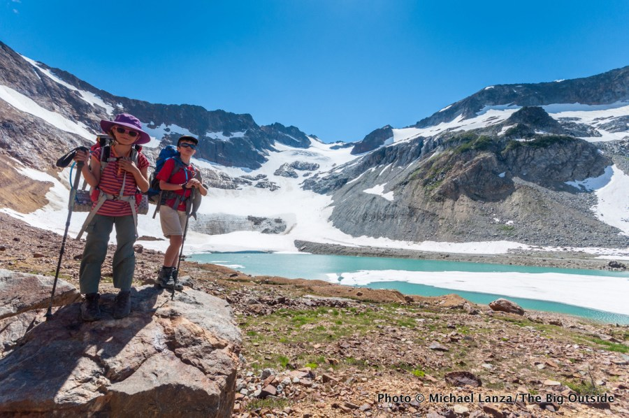 Two young kids backpacking at Upper Lyman Lakes in Washington's Glacier Peak Wilderness.