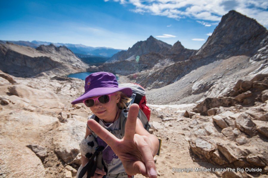 Young girl flashing peace sign backpacking in Sequoia National Park.