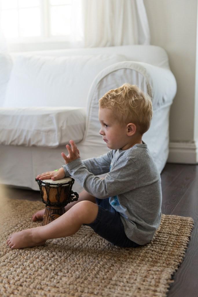 Toddler playing African drum