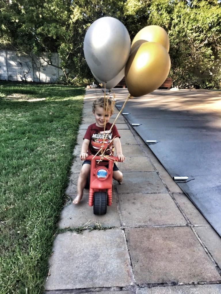 Toddler riding bike with balloons