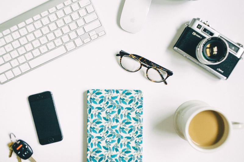 desk with keyboard, glasses, notebook and coffee
