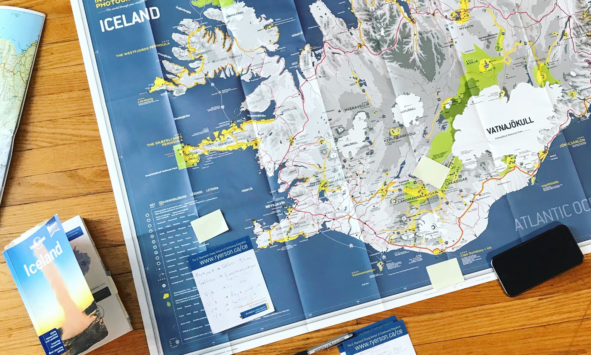 Photo of a map of Iceland next to a travel guide, a pint of beer, a notepad, and an iPhone