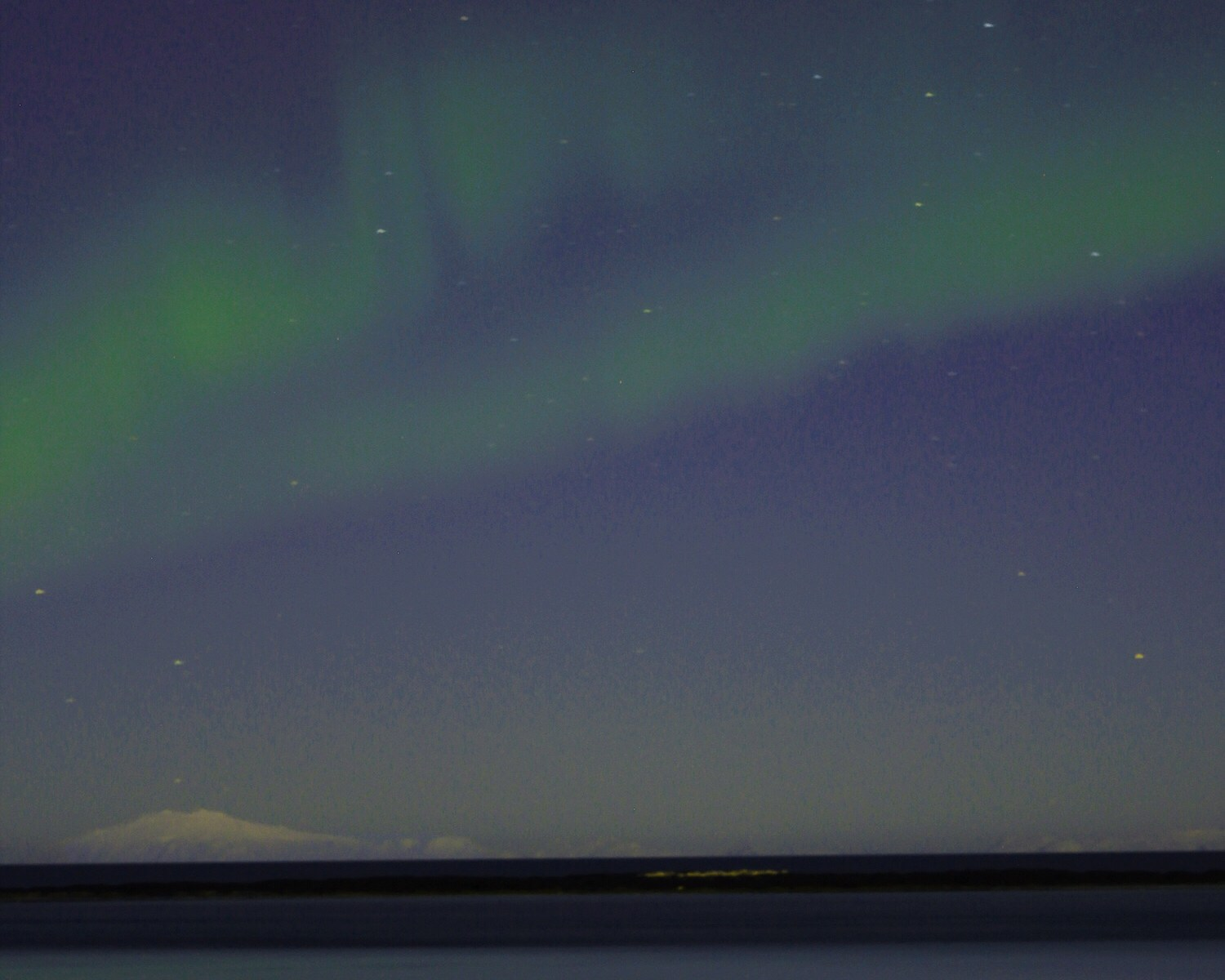 photo of the northern lights over a mountain
