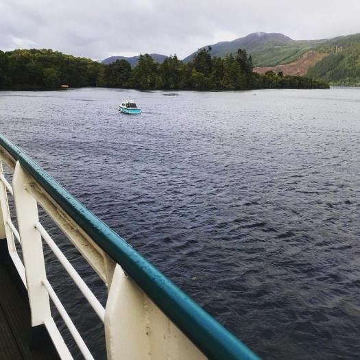 Photo of a small boat in the loch, as seen from the deck of a larger boat