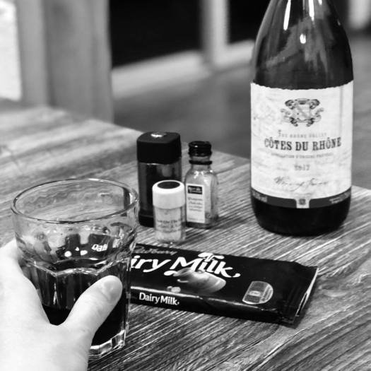Photo of a glass of wine next to a chocolate bar, a bottle, and small containers of salt, pepper, and oil