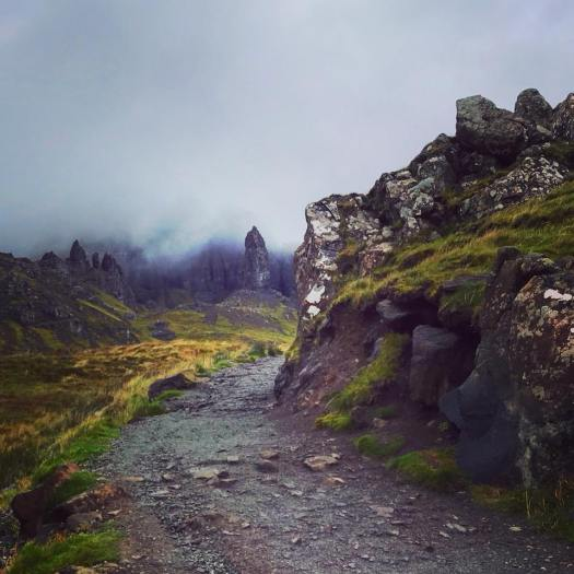 Photo of a path winding around rocks towards a tall erect stone surrounded by clouds