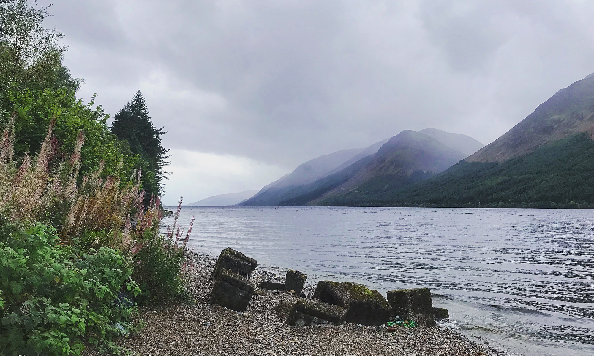 Photo of the shore of Loch Lochy with a pebble beach and misty mountains