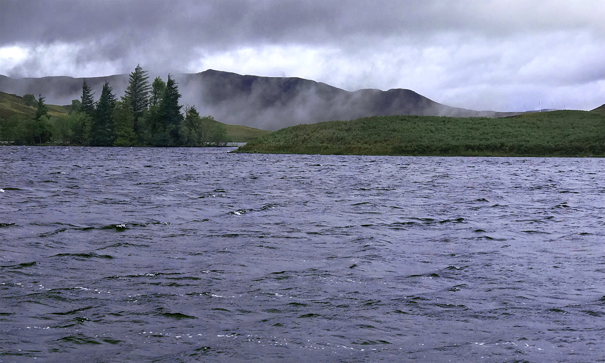 Photo of a loch and small islands shrouded in mist below mountains on a cloudy day