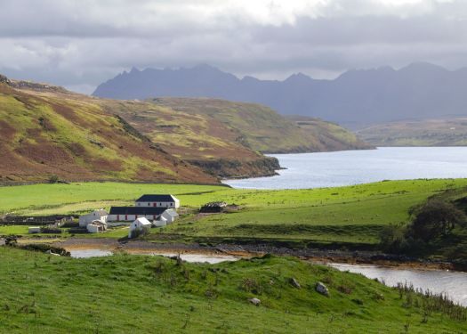 Photo of a farm by a loch and cliffs on a sunny day