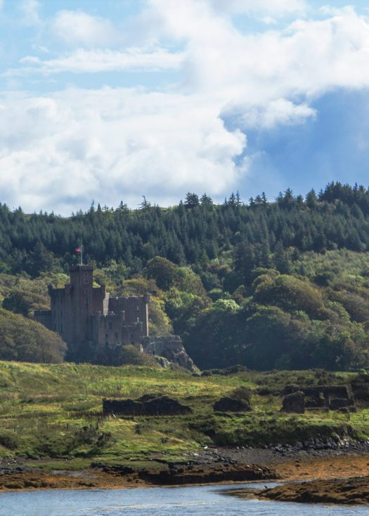 Photo of a rectangular castle nestled into a tree topped hill by water