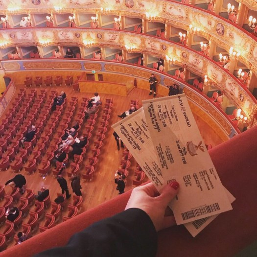 Photo of tickets to the opera held out over the railing looking down on floor seating at La Fenice
