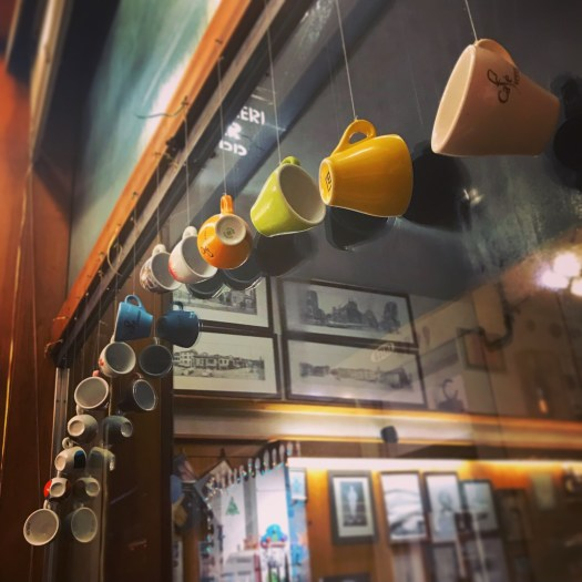 Photo of espresso cups hung on string around a window