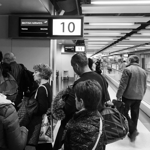 Photo of people lined up below an airport gate sign for British Airway to Venice