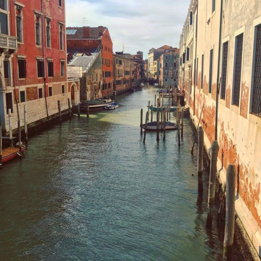 Photo of a wide canal in Venice with boats tied to poles in the water