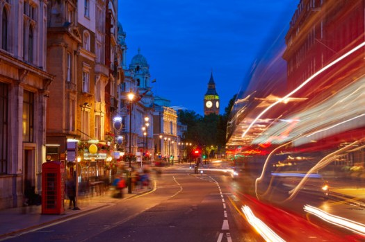 Photo of London at night with Big Ben, a red telephone booth, and the lights of a moving bus going by