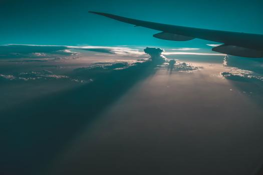 Photo of a plane wing in sunshine and clouds