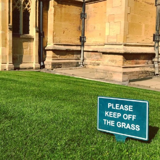"Photo of a sign that reads ""Please keep off the grass"""
