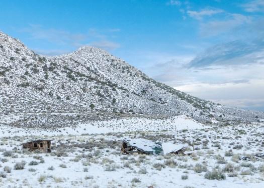 Photo of a run down hut beneath a snowy hill