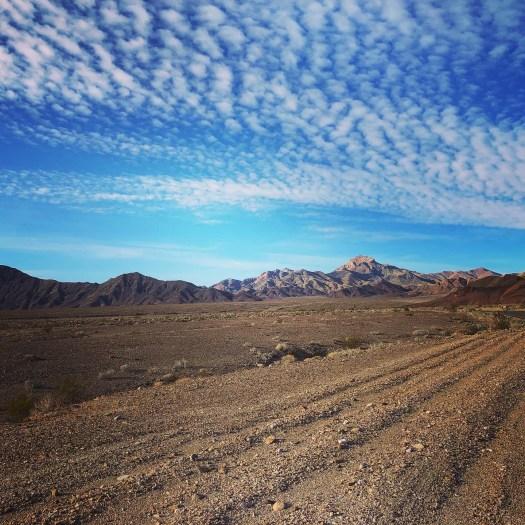 Photo of gravel and desert beneath barren mountains