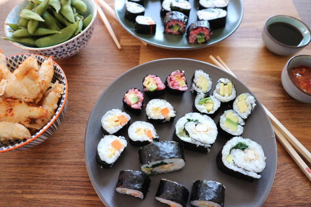 Sushi bunt gefüllt mit Süßkartoffel, Avocado, Gurke und Tempura Hühnchen, dazu Edamame und mehr Hühnchen