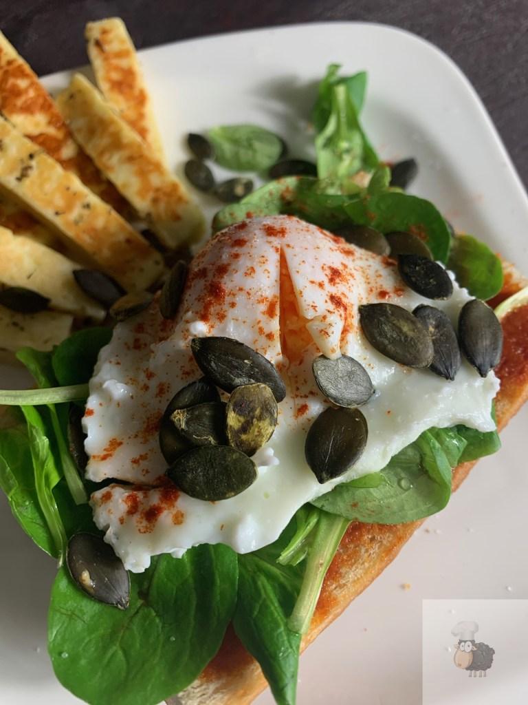 Sandwich mit Tomaten-Butter Creme, Feldsalat, pochiertem Ei, Kürbiskernen und Grillkäse