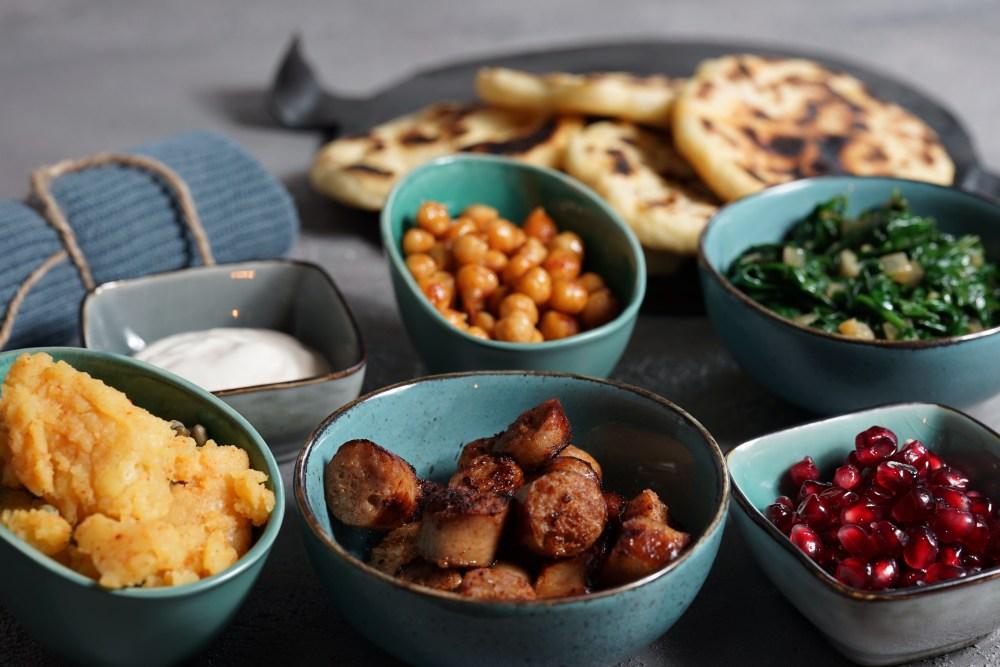 Naan International mit Kartoffelpaste, Yoghurt, Knusperkichererbsen, Bratwurst, Spinat und Granatapfel