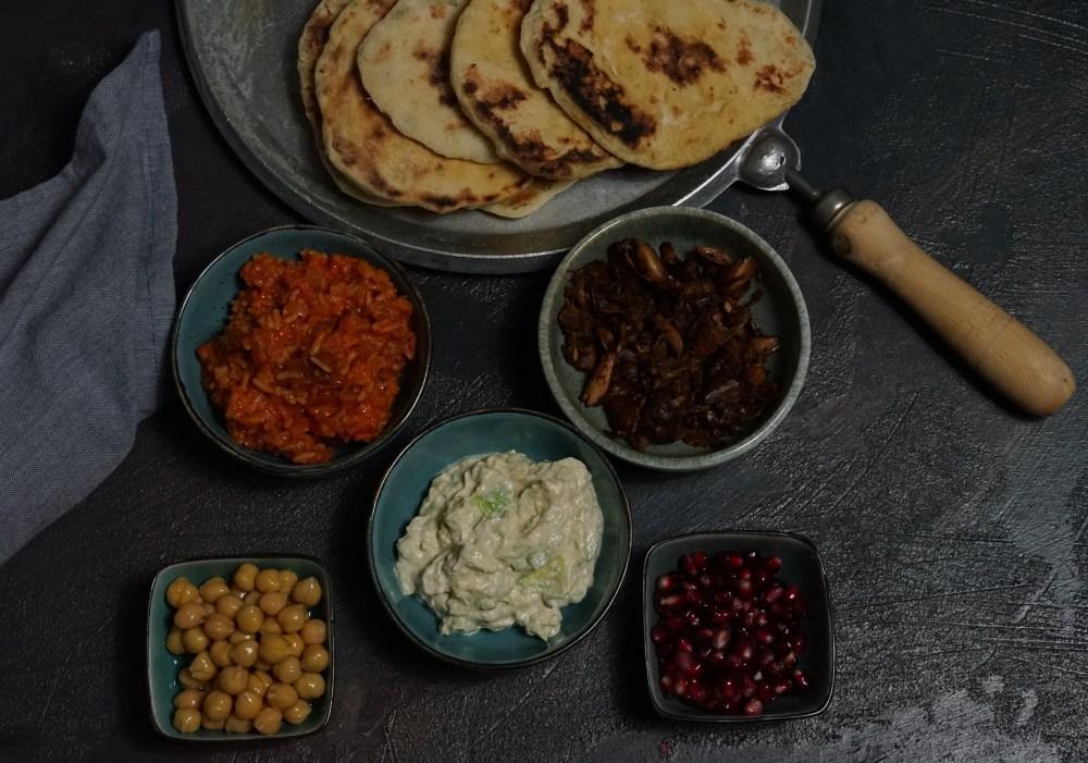 Naan mit Tomatenreis, Jackfruit, Kichererbsen, Avocadocreme und Granatapfel