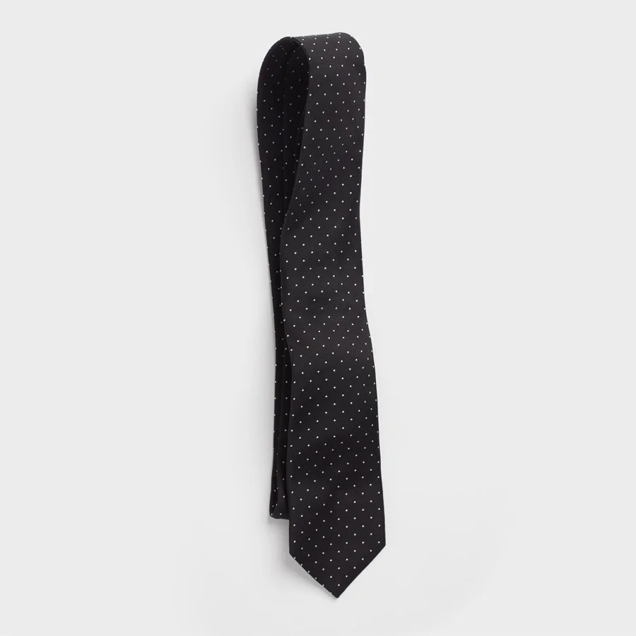Black necktie by The Black Tux, made of 100% silk with white pindot motif.