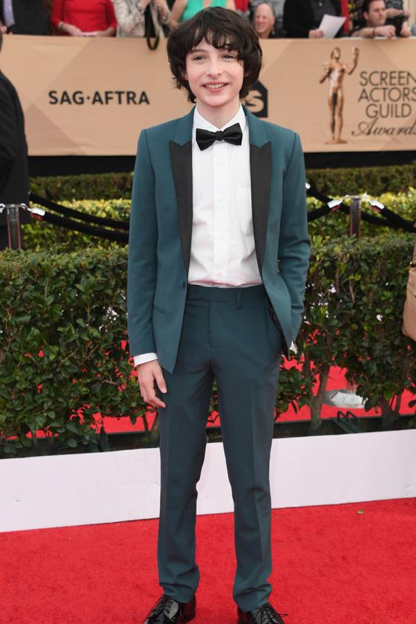 Finn Wolfhard in an emerald prom tux.