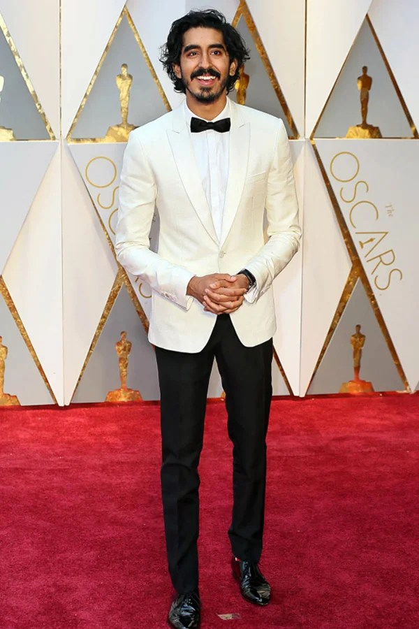 Dev Patel, also wearing a white dinner jacket prom tux.