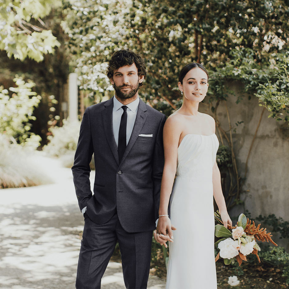 Man in charcoal suit by The Black Tux with bride in white dress.