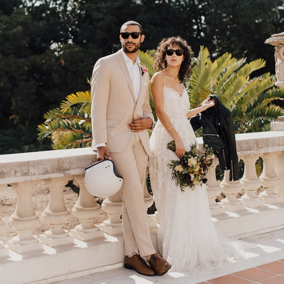 Man in tan wedding suit with woman in white dress.