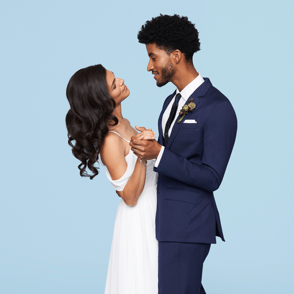 Groom dancing with bride in blue wedding suit.