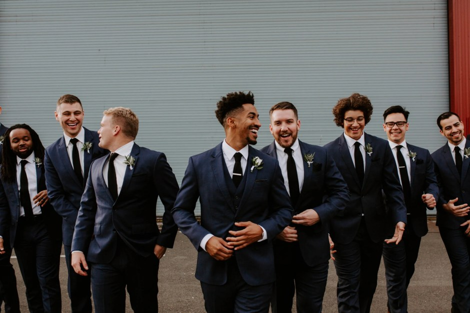 groom in blue suit spring wedding attire with vest and black tie with matching groomsmen attire