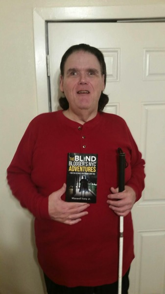 Me holding my book The Blind Blogger s NYC Adventures